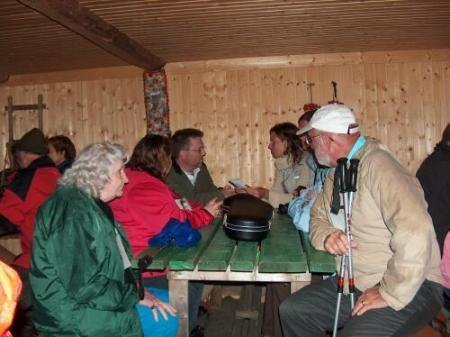 People gather in the hut behind the Dedication site