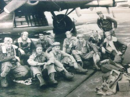 James is sitting down with his knees up and arms crossed.  The rest of crew names unknown - 301st BG, Army Air Corps Library and Museum